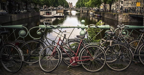 Bicycles resting against bridge railing on a canal in Amsterdam