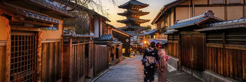 Two women in traditional dress standing on a Kyoto street at sunset