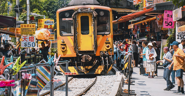 Yellow train passing through Shifen Old Street, Taiwan