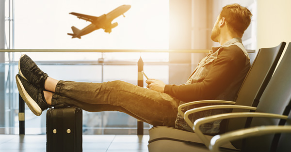 Young man sitting in airport looking at plane taking off