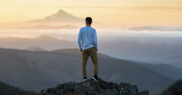 Man looking at the landscape from a mountain peak