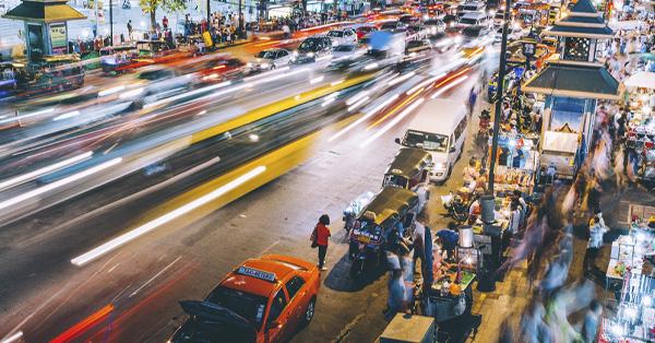 Busy street and sidewalk in Bangkok at night