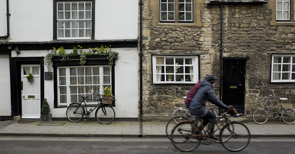 Two people riding bikes along a street in Cambridge, England