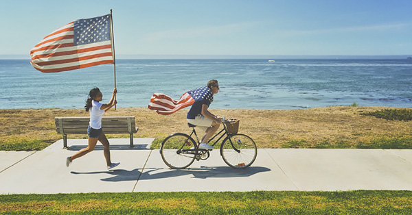 Girl chasing a man on a bike, both carrying USA flags