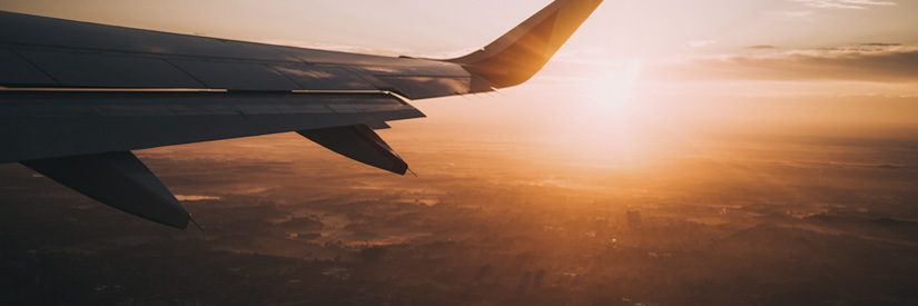 Plane wing shown in flight during sunset